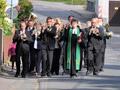 Pastorin, Posaunenchor und Kinder mit Erntekrone und Erntegaben marschieren vom Pfarrhaus zur Kirche